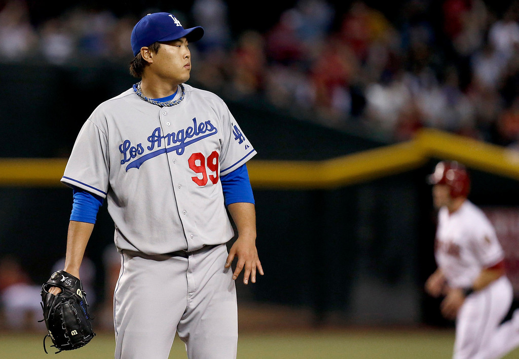 . Los Angeles Dodgers\' Hyun-Jin Ryu (99) looks at a Arizona Diamondbacks\' Paul Goldschmidt two-run home run as Diamondbacks\' A.J. Pollock, right, runs the bases in the first inning of a baseball game on Monday, Sept. 16, 2013, in Phoenix. Diamondbacks won 2-1.   (AP Photo/Ross D. Franklin)
