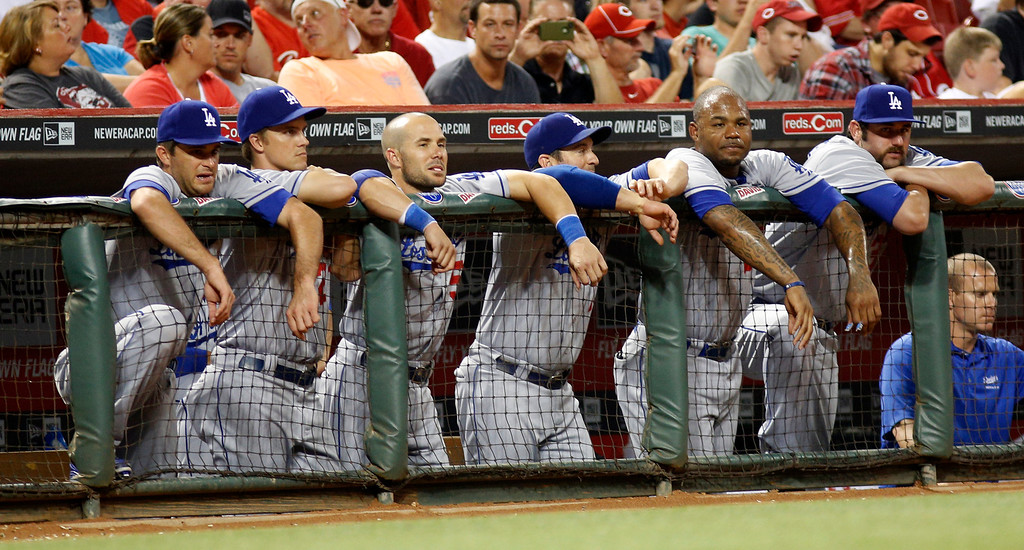 . Los Angeles Dodgers players lean on the dugout rail as they watch a baseball game against the Cincinnati Reds, Sunday, Sept. 8, 2013, in Cincinnati. Reds won 3-2.   (AP Photo/David Kohl)