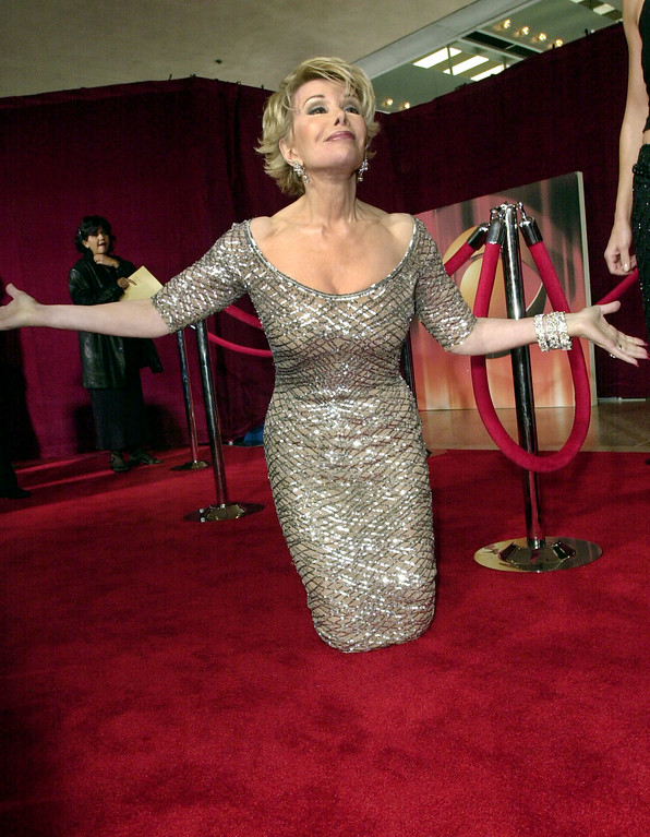 . Joan Rivers of E! Television kneels in a gesture to welcome back the red carpet before the start of the 53rd annual Primetime Emmy Awards at the Shubert Theatre on Sunday, Nov. 4, 2001, in Los Angeles. (AP Photo/Kim D. Johnson)