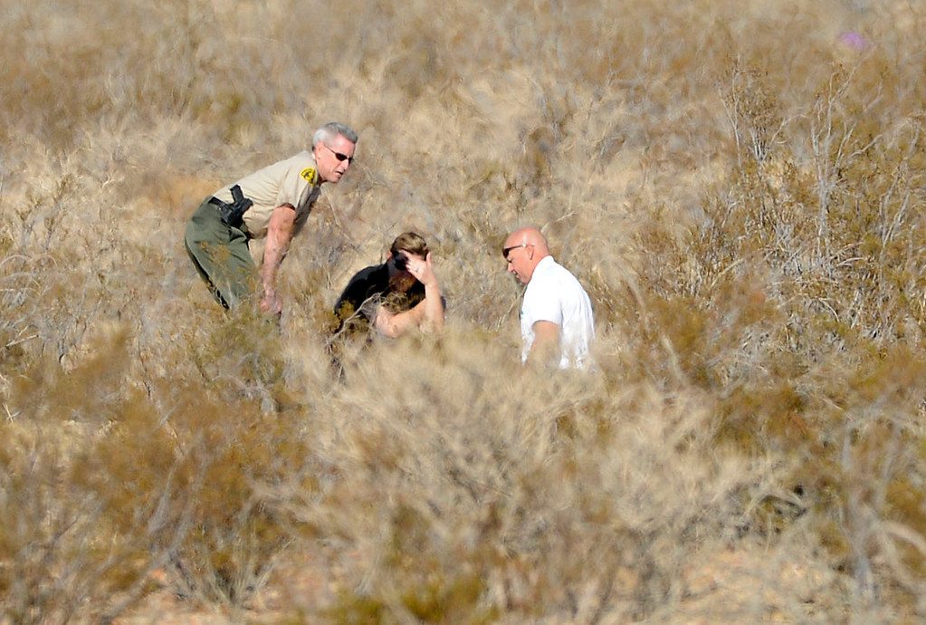 . San Bernardino County Sheriff John McMahon (left) looks on as detectives investigate a scene off of Quarry Road, near Interstate 15, in the desert north of Victorville Wednesday morning November 13, 2013 after multiple skelton remains were found. The investigation is on going.   (Will Lester/Inland Valley Daily Bulletin)
