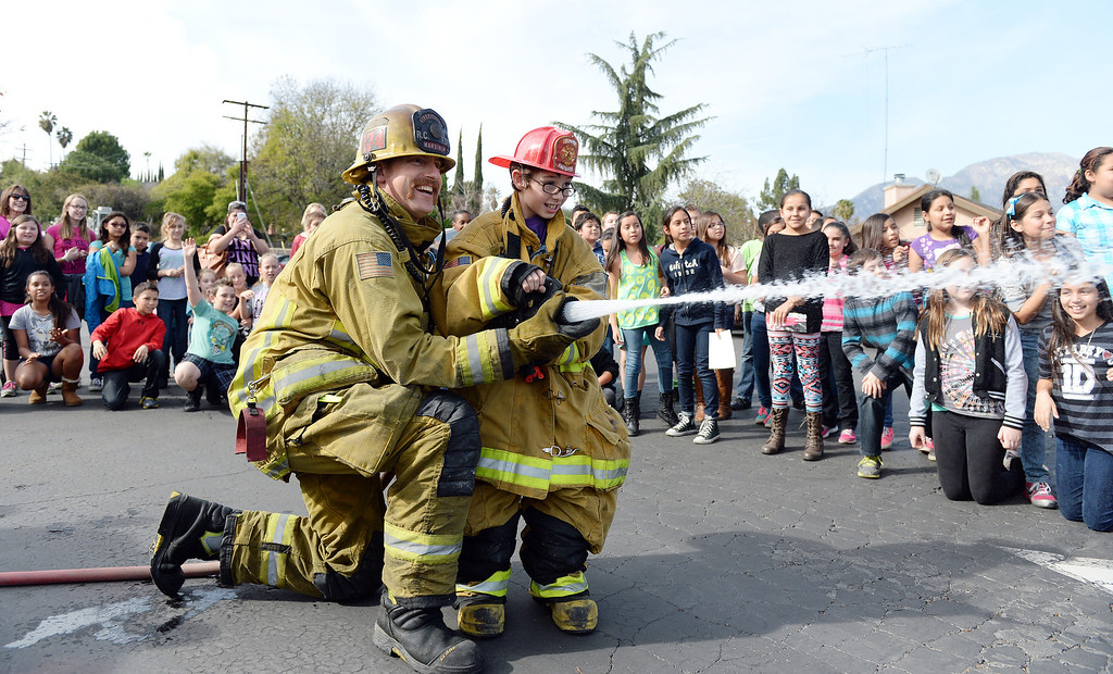 . Valle Vista Elementary School fifth grader Hayden Pestel, 10, is assisted by Rancho Cucamonga firefighter Nick Maksimuk while he sprays water Tuesday at the school. Pestel was recognized as a hero Tuesday February 11, 2014 by the Rancho Cucamonga fire department. Pestel awoke his sleeping grandfather Thursday night after the laundry room in his home caught fire allowing them both to escape the fire without injury. Damage to the home was set at $230,000. (Will Lester/Inland Valley Daily Bulletin)