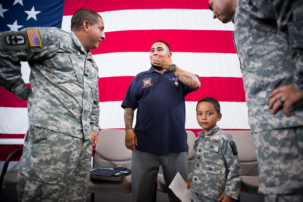 . After receiving his Purple Heart Sgt. Luis Bardales, center, visits with the man he saved, gunner Gabriel Herrera, left, and his son Joshua, 5, and his Lt. Col. Dan Bout at the Army National Guard in Azusa Saturday, July 12, 2014. Bardales was wounded by a roadside IED in Baghdad, Iraq and saved  Herrera by pulling him out of their Humvee before another IED explosion. (Photo by Sarah Reingewirtz/Pasadena Star-News)