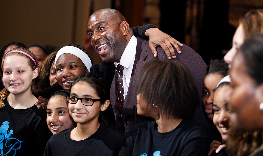""". Businessman and former NBA star Magic Johnson smiles for a picture with members of an AAU girls basketball team in Saginaw, Mich., Tuesday, April 29, 2014. Johnson returned to Saginaw for the third annual \""""Magic of a Promise\"""" fundraiser for the Saginaw Promise Scholarship. (AP Photo/The Saginaw News, Neil Barris)"""