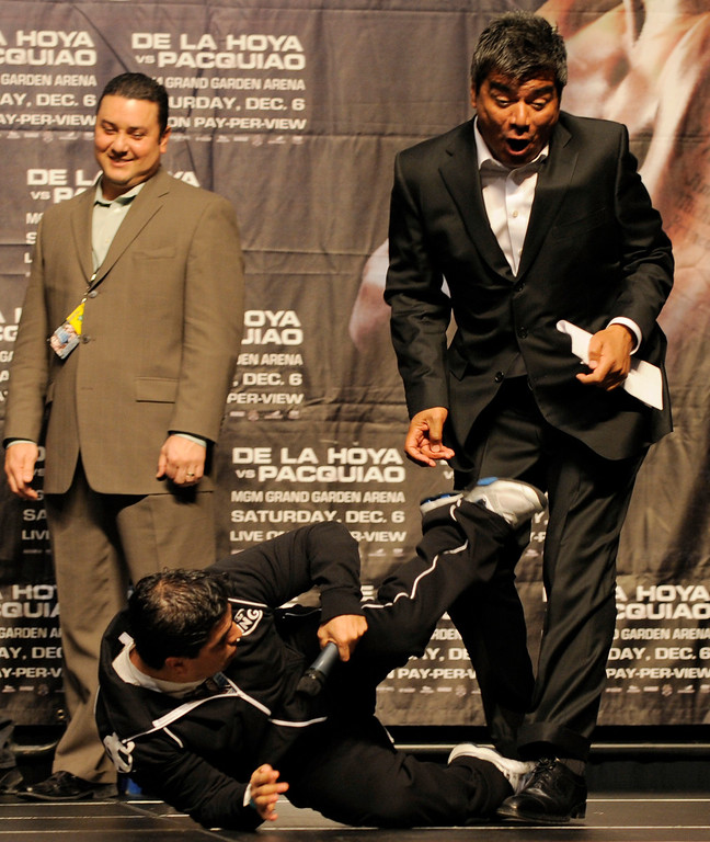 ". Comedian Eddie ""Piolin\"" Sotelo pretends to kick comedian George Lopez as they entertain the crowd during the weigh-in for the Oscar De La Hoya-Manny Pacquiao welterweight boxing match in Las Vegas, Friday, Dec. 5, 2008.  (AP Photo/Mark J. Terrill)"