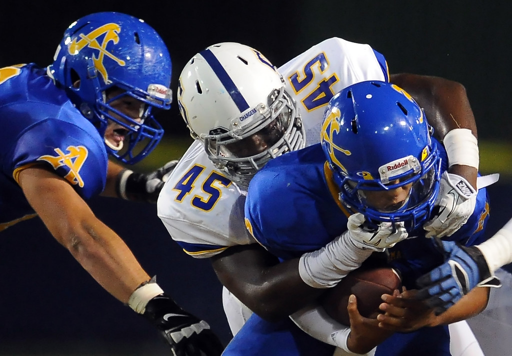 . Charter Oak\'s Khylan Brooks (45) tackles Bishop Amat quarterback Koa Haynes (C) in the first half of a prep football game at Bishop Amat High School in La Puente, Calif. on Friday, Sept. 20, 2013.    (Photo by Keith Birmingham/Pasadena Star-News)
