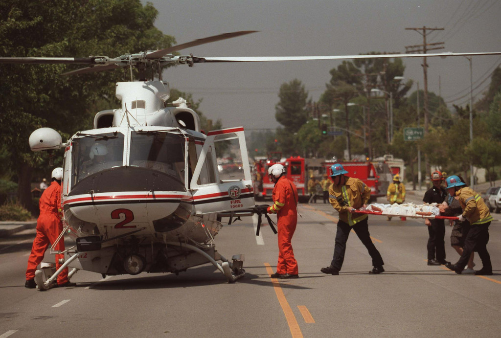 . A male child victim is carried by paramedics to a helicopter which will take him to Children\'s Hospital Los Angeles.  Five victims, three male children and two female adults, were shot at the North Valley Jewish Community Center in Granada Hills, California Tuesday morning, August 10, 1999.   Los Angeles Daily News file photo.