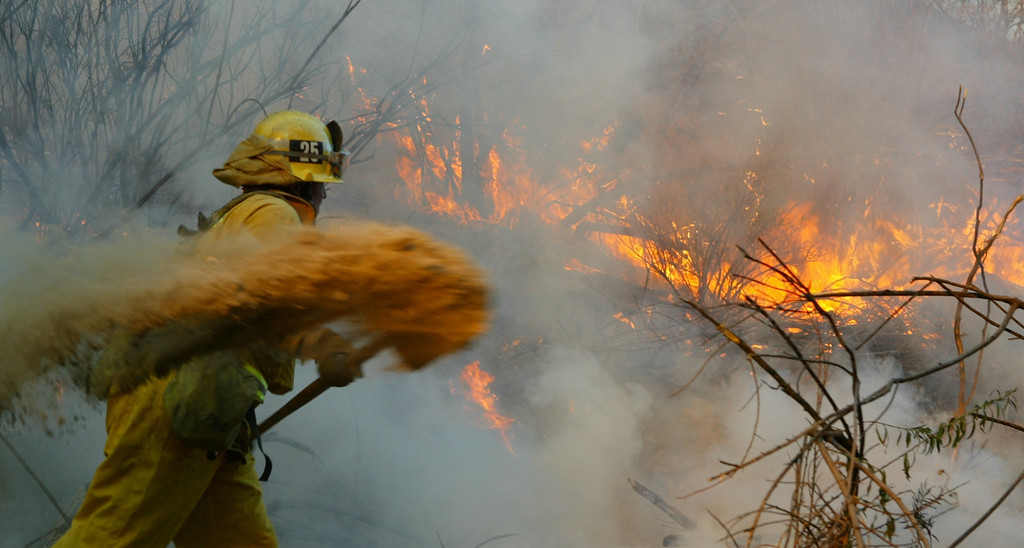 . 10-24-03...Val Verde Park fire...Photo of LA county firefighter as he throws dirt to stop the spreading  on a 200+acre brush fire that is still burning, more info from fire dept.Photo by Gene Blevins/LA Daily news