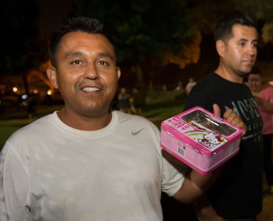 . Richard Espinoza, of Whittier, shows the Hello Kitty lunchbox he found with $100 as Cash hunters search all over Penn Park in Whittier for #HiddenCash stashed in Pez dipsensers and lunch boxes in the park bushes on Thursday July 10, 2014. Hundreds of people searched through the bushes all over the park. (Staff Photo by Keith Durflinger/Pasadena Star-News)