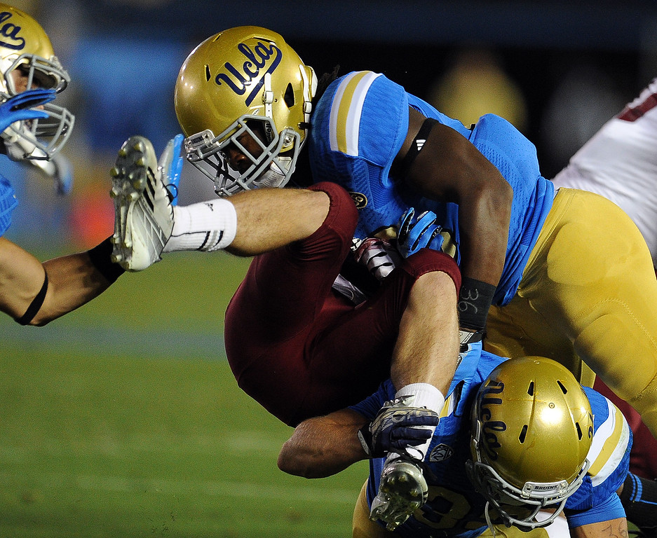 . New Mexico State wide receiver Adam Shapiro is tackled by UCLA linebacker Jayon Brown (19) on a punt return during the first half of their college football game in the Rose Bowl in Pasadena, Calif., on Saturday, Sept. 21, 2013.   (Keith Birmingham Pasadena Star-News)