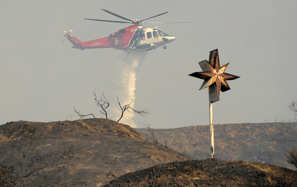 . A helicopter makes a water drop on the hillside behind the Self Realization Fellowship Glendale Temple on Chevy Chase.  A brush fire burned nearly 75 acres in an area north and east of the 134 and 2 freeways in Glendale. Residents on East Chevy Chase, east of the 2 freeway were evacuated as helicopters, hand crews and firefighters battled the fire that burned through the mountains and canyons. Glendale, CA 5/3/2013(John McCoy/Staff Photographer)