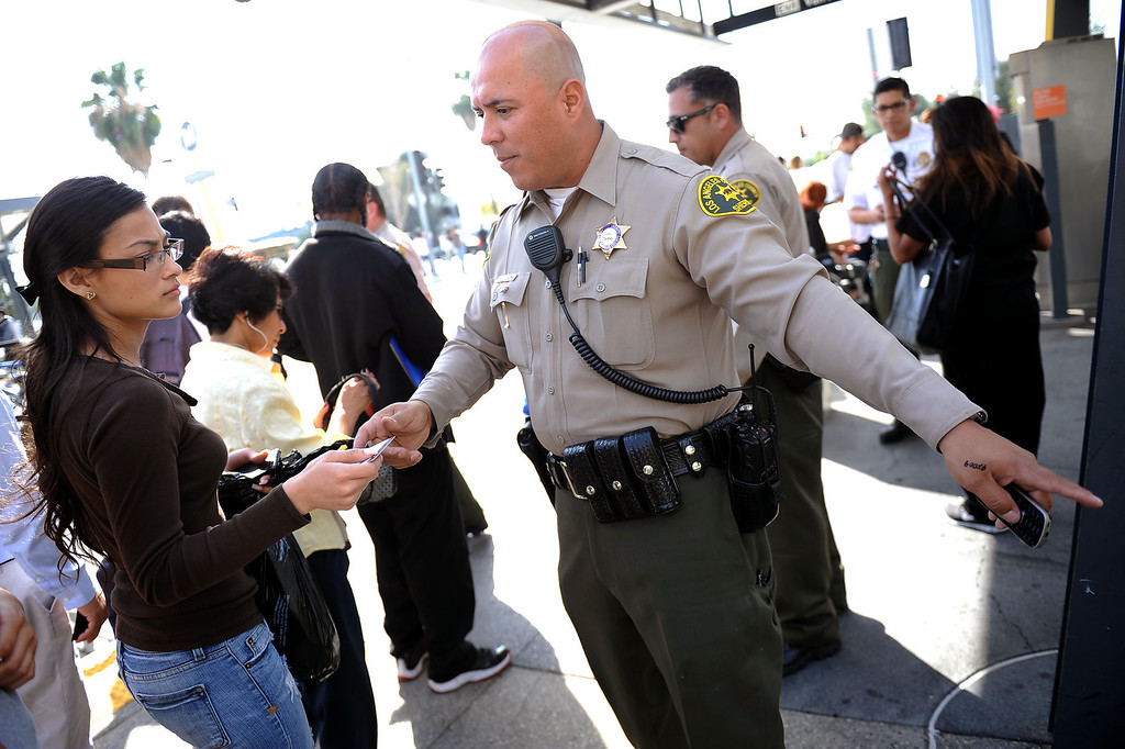 . LA County Sheriff deputy Carlos Valencia prepares to issue a fare evasion citation during an Orange Line fare enforcement operation at the Van Nuys Orange Line Station February 25, 2014.  Officials from Metro and the Los Angeles Sheriff\'s Department Transit Services Bureau announced a new two-pronged effort to cut down on fare-evaders on the Orange Line by improving communications and beefing up enforcement.(Andy Holzman/Los Angeles Daily News)