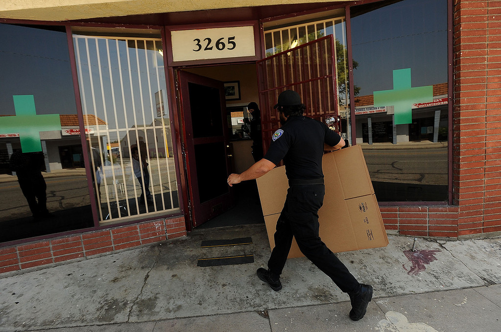 . A San Bernardino Police officer brings in evidence boxes during a raid on a marijuana dispensary along the 3200 block of North E Street in San Bernardino May 9, 2013.  GABRIEL LUIS ACOSTA/STAFF PHOTOGRAPHER.