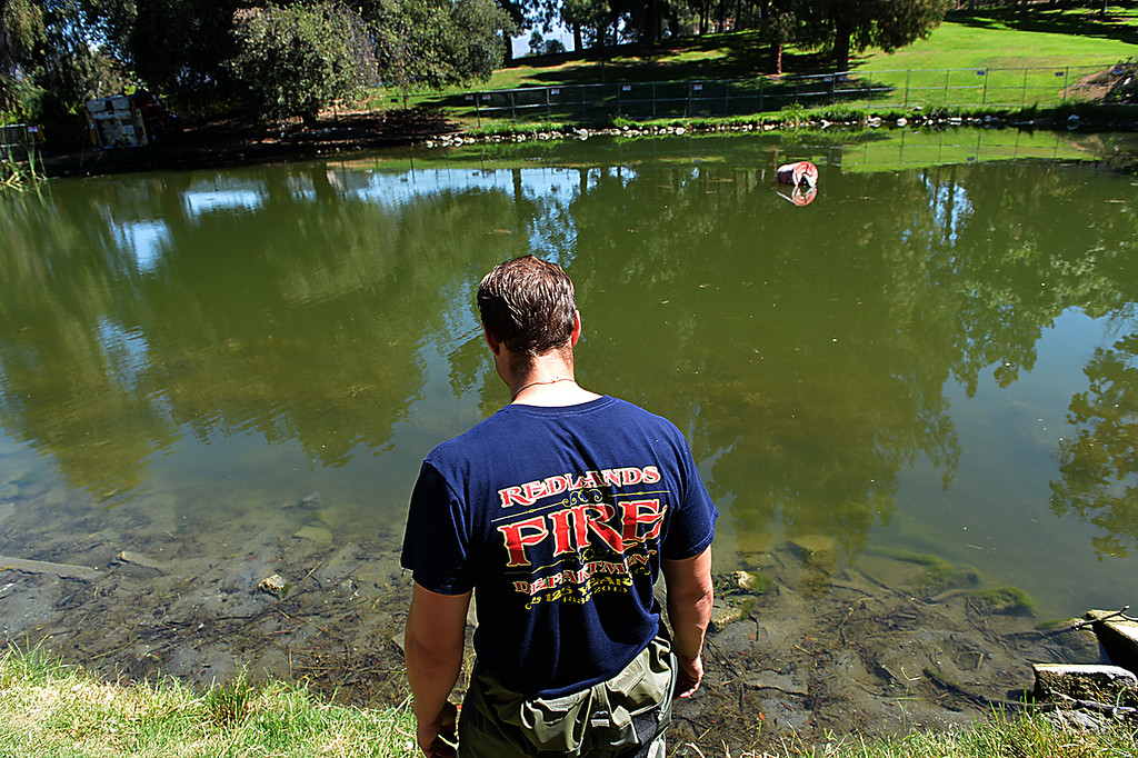 """. Jason Dressel, a Redlands firefighter, monitors the draining of a pond at Ford Park. The Redlands Fire Department is assisting the Rotary Clubs Tuesday July 9, 2014 in a project intended to revitalize the lower pond at Ford Park. The fire department is making use of the project to conduct training as well. The training called \""""drafting\"""" is a process used to draw water from ponds and other bodies of water in the event the city\'s water system is not available. (Photo by Rick Sforza/Redlands Daily Facts)"""