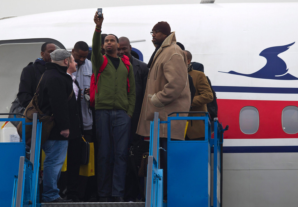 """. U.S. basketball player Jerry Dupree, center, uses a mobile camera to take a photograph as he and fellow players including former NBA player Vin Baker, right, arrive at the international airport in Pyongyang, North Korea, Monday, Jan. 6, 2014. Dennis Rodman arrived in the North Korean with a squad of former basketball stars in what Rodman calls \""""basketball diplomacy,\"""" although U.S. officials have criticized his efforts. (AP Photo/Kim Kwang Hyon)"""
