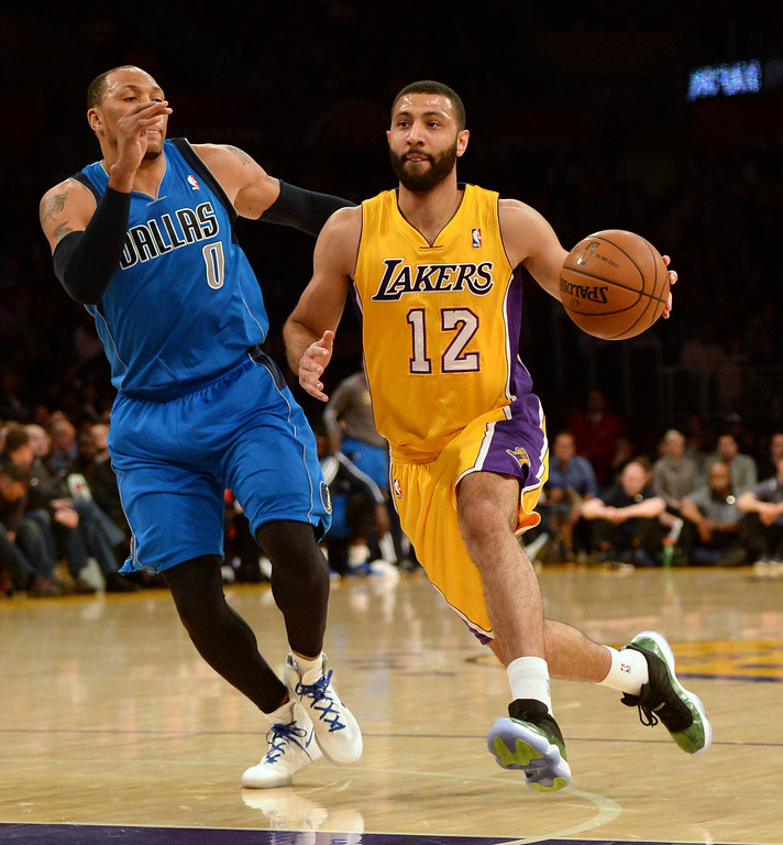 . Los Angeles Lakers guard Kendall Marshall (12) drives down the lane past Dallas Mavericks forward Shawn Marion (0) in the first quarter during an NBA basketball game in Los Angeles, Calif., on Friday, April 4, 2014.  (Keith Birmingham Pasadena Star-News)