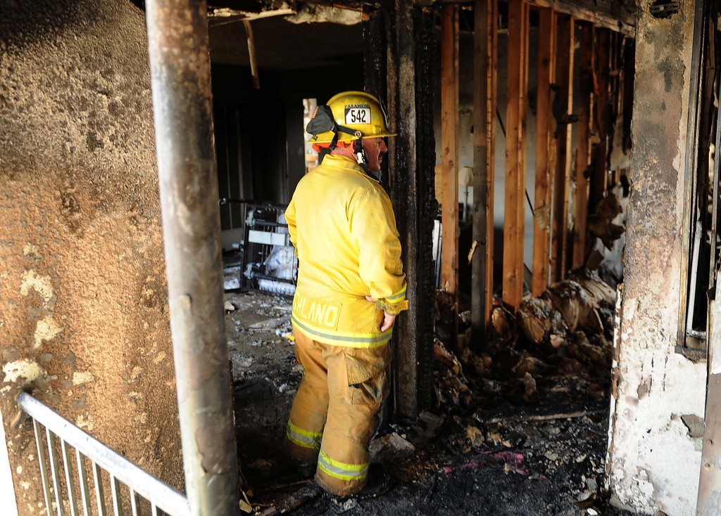 . Cal Fire firefighter Lee Fonseca searches through a burned-out apartment after a fire at the complex Sunday morning displaced 72 residents in Highland on Sunday. (LaFonzo Carter/Staff Photographer)