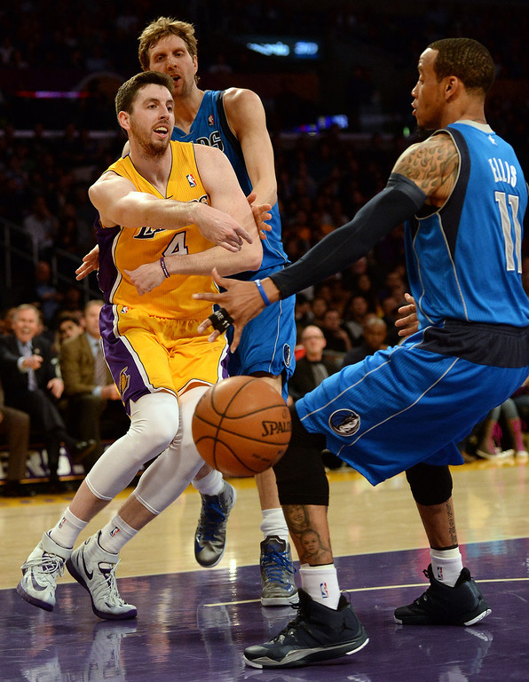 . Los Angeles Lakers forward Ryan Kelly (4) passes past Dallas Mavericks forward Dirk Nowitzki (41) and guard Monta Ellis (11) in the first quarter during an NBA basketball game in Los Angeles, Calif., on Friday, April 4, 2014.  (Keith Birmingham Pasadena Star-News)