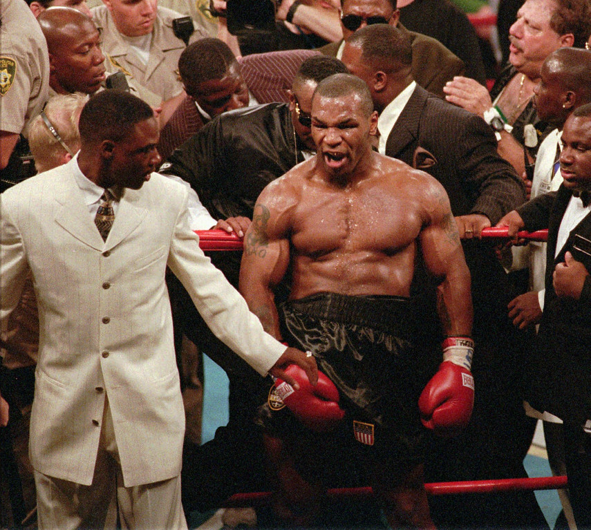 . Mike Tyson, center, reacts to the crowd as he leaves the ring following his bout with WBA heavyweight champion Evander Holyfield, Saturday night, June 28, 1997, at the MGM Grand Garden in Las Vegas. Tyson was disqualified after biting Holyfield\'s ear twice in the third round. (AP Photo/Lennox McLendon)