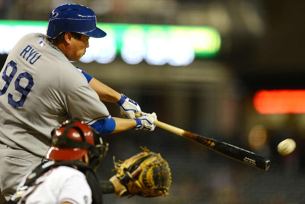 . PHOENIX, AZ - SEPTEMBER 16:  Hyun-Jin Ryu #99 of the Los Angeles Dodgers drives the ball to right field against the Arizona Diamondbacks at Chase Field on September 16, 2013 in Phoenix, Arizona.  (Photo by Norm Hall/Getty Images)
