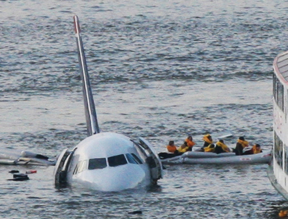 """. FILE - In this Jan. 15, 2009 file photo, passengers in an inflatable raft move away from US Airways Flight 1549 that went down in the Hudson River in New York. Capt. Chesley \""""Sully\"""" Sullenberger III, First Officer Jeff Skiles and some passengers who were on the plane on Wednesday, Jan. 15, 2014 are expected to join some of the ferry crews who rescued them from the cold waters five years ago. (AP Photo/Bebeto Matthews, File)"""