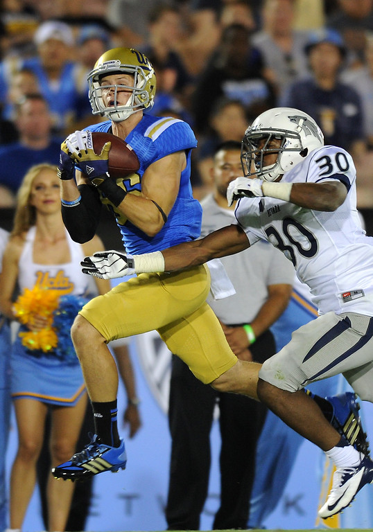 . UCLA WR Reed Buce hauls in a pass against Nevada\'s Tere Calloway in the fourth quarter, Saturday, August 31, 2013, at the Rose Bowl. (Michael Owen Baker/L.A. Daily News)