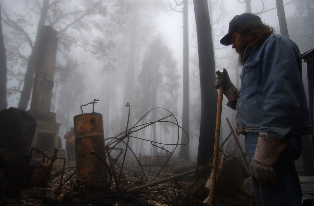 . Ten years ago this month the arson caused Old Fire, fanned by Santa Ana winds burned thousands of acres, destroyed hundreds of homes and caused six deaths. The fire burned homes in San Bernardino, Highland, Cedar Glen, Crestline, Running Springs and Lake Arrowhead and forced the evacuation of thousand of residents. Richard Mortimore, of San Bernardino, looks over his grandmother\'s home in Crestline, as residents return to their homes to sift through the ashes Monday, Nov 3rd 2003 morning. (Staff file photo/The Sun)