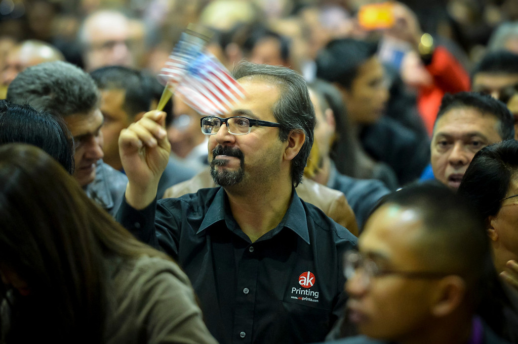. New US Citizens wave US flags after being sworn in as US citizens at the Los Angeles Convention Center Tuesday, December 17, 2013.  3,793 immigrants were sworn in as New US citizens at the ceremony.  ( Photo by David Crane/Los Angeles Daily News )