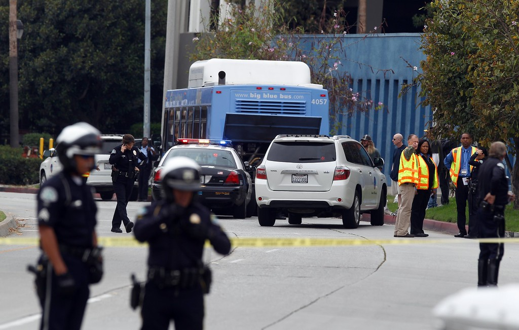 . Investigators look at a Santa Monica City Bus that was shot at in Santa Monica, Calif. Friday, June 7, 2013. Someone fired gunshots near the campus of Santa Monica College shortly before noon Friday, police said, and several people were reported to be wounded. (AP Photo/Damian Dovarganes)