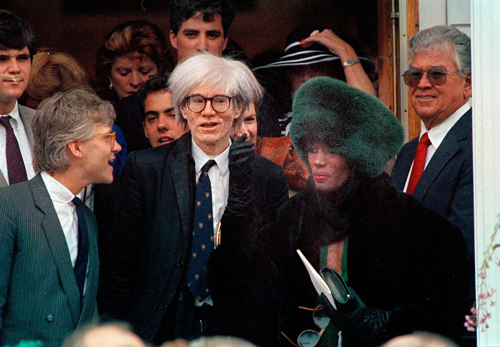 . Artist Andy Warhol, center, and Grace Jones, right, wearing fur hat, are seen attending Maria Shriver\'s wedding to Arnold Schwarzenegger in Hyannisport, Mass., April 26, 1986. Others are unidentified.  (AP Photo)