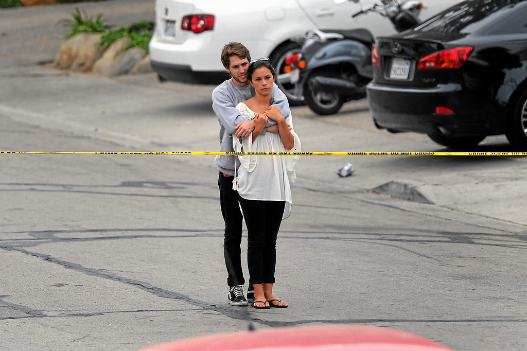 . A couple looks at the scene where the gunman\'s car crashed on Del Playa Drive in Isla Vista, Saturday, May 24, 2014. (Photo by Michael Owen Baker/Los Angeles Daily News)