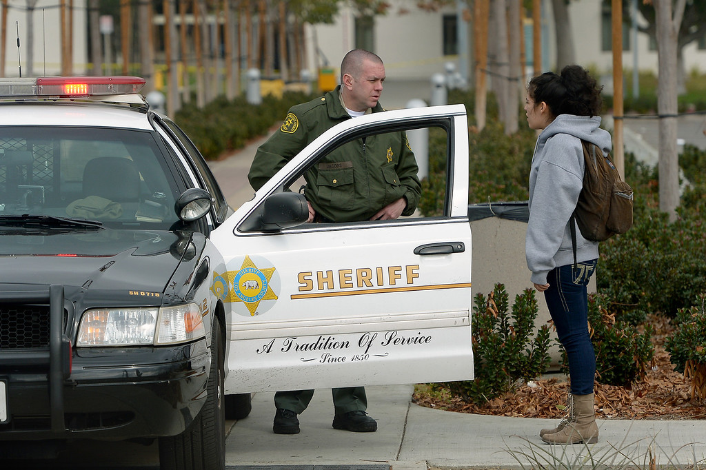 . An L.A. County Sheriff talks to a student at an entrance to Valley College after the campus was closed due to a shooting threat, Thursday, February 6, 2014. A 19-year-old woman was arrested just before 11 a.m. in connection with a phone call threatening a shooting on the campus that prompted the cancellation of all classes Thursday morning. (Photo by Michael Owen Baker/L.A. Daily News)