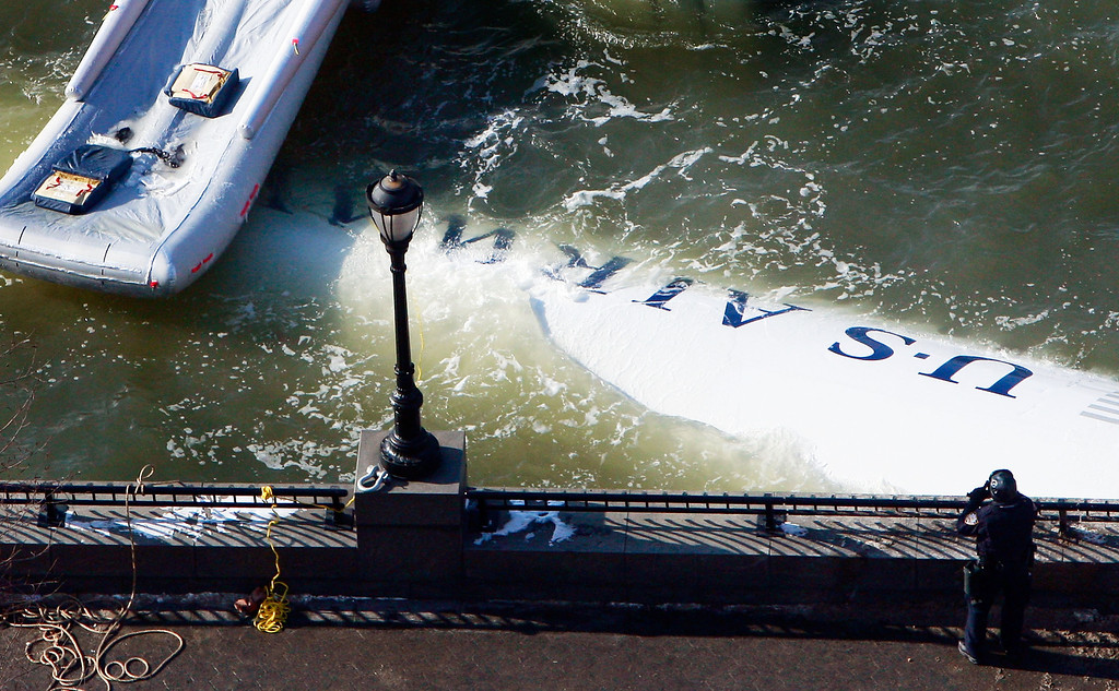 """. NEW YORK - JANUARY 16:  The wreckage of US Airways flight 1549 floats in the Hudson River as investigations into the accident continue on January 16, 2009 near Battery Park City in New York City. Yesterday the pilot, Chesley \""""Sully\"""" Sullenberger, 57, of the damaged plane landed the aircraft in the river with all 155 people aboard surviving.  (Photo by Mario Tama/Getty Images)"""