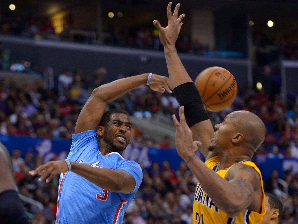 . Los Angeles Clippers guard Chris Paul passes the ball past Indiana Pacers forward David West during the second half of an NBA basketball game, Sunday, Dec. 1, 2013, in Los Angeles. (AP Photo/Mark J. Terrill)