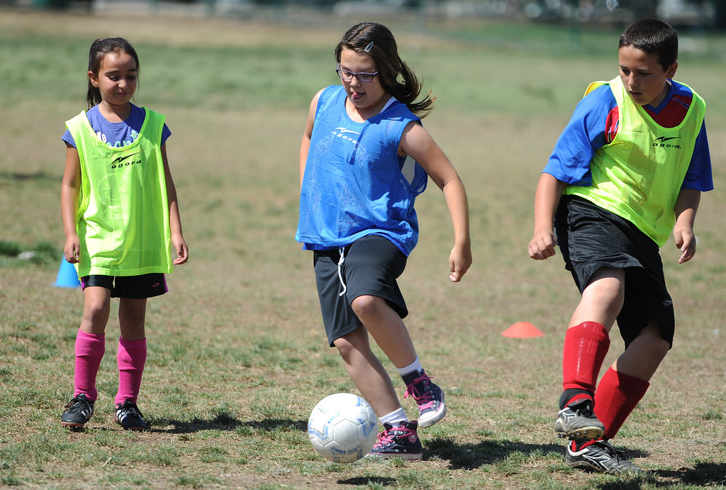 """. Caitlyn Burnett, center, kicks the ball between Heidi Reyes and Jacob Eskelin. In honor of the AYSO\'s 50th anniversary as the nation�s most active and open youth soccer organization, kids at Balboa Park in Encino will join efforts around the country Saturday--over 500,000 players,125,000 volunteers,100 community-based events and a national soccer festival--to set a world record for the \""""largest pickup game on Earth.\"""" Encino, CA. 5/3/2014(Photo by John McCoy / Los Angeles Daily News)"""