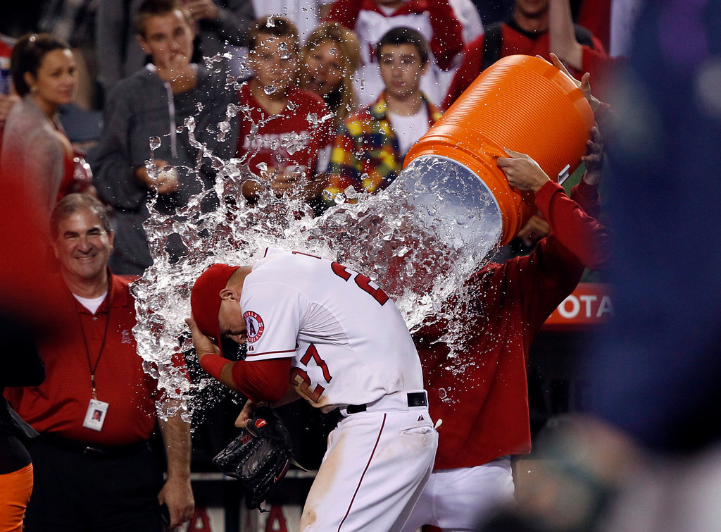 . Los Angeles Angels\' Mike Trout, center, is doused with cold water by teammates after hitting for the cycle against the Seattle Mariners during 12-0 win in a baseball game Tuesday, May 21, 2013 in Anaheim.    (AP Photo/Alex Gallardo)