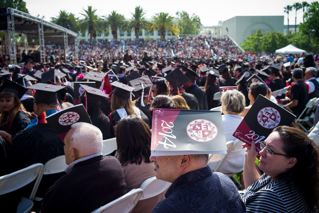 . Spectators shield themselves from the sun at graduation ceremonies at Cal State Northridge Monday, May 19, 2014.  ( Photo by David Crane/Los Angeles Daily News )