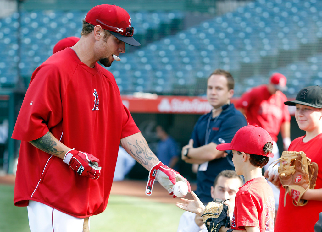 . Los Angeles Angels right fielder Josh Hamilton, left, signs autographs for kids prior to playing against the Seattle Mariners in a baseball game Tuesday, May 21, 2013 in Anaheim.    (AP Photo/Alex Gallardo)