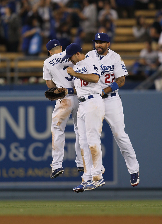 . (L-R) Skip Schumaker #3, Andre Ethier #16 and Matt Kemp #27 of the Los Angeles Dodgers celebrate after defeating the Miami Marlins 7-1 in their MLB game at Dodger Stadium on May 11, 2013 in Los Angeles, California.  (Photo by Victor Decolongon/Getty Images)
