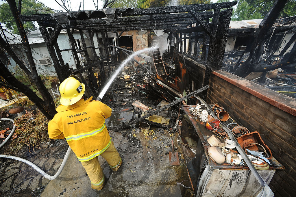 . Hotspots are doused after a structure fire damaged two homes in the 17800 block of Vanowen St. in Reseda, CA April 10, 2014.(Andy Holzman/Los Angeles Daily News)