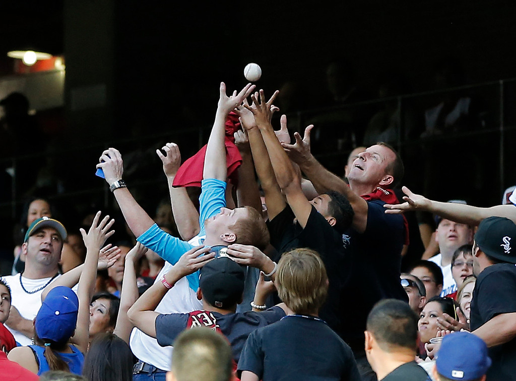 . Fans reach for a foul ball hit by Los Angeles Dodgers\' Matt Kemp during the first inning of a baseball game against the Arizona Diamondbacks, Saturday, April 13, 2013, in Phoenix. (AP Photo/Matt York)