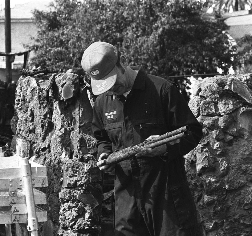 . A Los Angeles police officer holds part of a shotgun recovered from the burned wreckage of a south-central Los Angeles house during an investigation on May 18, 1974.   Police fired tear gas shells in the belief that the house was occupied by three members of the Symbionese Liberation Army.  They found no one inside.  (AP Photo)