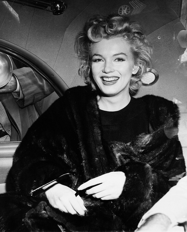 . In this June 2, unknown year, file photo, actress Marilyn Monroe smiles in a car after arriving tousled from an all-night plane flight from Hollywood to Idlewild Airport, in New York. The actress said she planned to rest in New York before going to England to make a new movie with Sir Laurence Olivier. In late 2012, the FBI has released a new version of files it kept on Monroe that reveal the names of some of her acquaintances who had drawn concern from government officials and members of her entourage over their suspected ties to communism. (AP Photo, File)