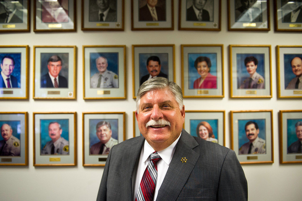 . L.A. County Interim Sheriff John Scott stands by portraits of retired chiefs and division chiefs at L.A. County Sheriff\'s headquarters in Monterey Park. His portrait is behind his right shoulder. (Photo by Michael Owen Baker/L.A. Daily News)