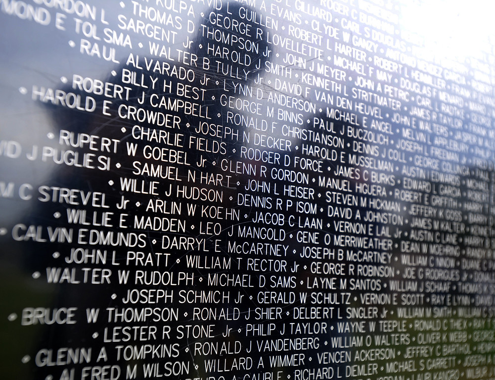 ". Visitors look at the names on the ""Wall that Heals\"" traveling replica of the Vietnam Veterans Memorial wall at La Habra High School in La Habra on Thursday July 11, 2013. The wall will be in the stadium until the closing ceremony on Sunday. (SGVN/Staff Photo by Keith Durflinger)"