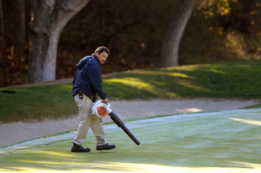 . A greenskeeper uses a leaf blower to melt frost on the 9th green prior to the start of the first-round of Tiger Woods\' Northwestern Mutual World Challenge at Sherwood Country Club in Thousand Oaks, CA Thursday December 5, 2013.  Frist-round play was delayed an hour due to icy conditions on the course.(Andy Holzman/Los Angeles Daily News)