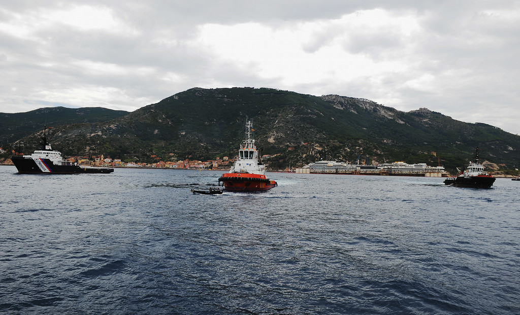 . The tugs towing the wrecked ship Costa Concordia are seen during refloating operations on July 14, 2014 in Isola del Giglio, Italy. On the first day of the operation the wreck will be partially refloated by 2 metres from the platfoms that support it and will be moved approximately 30 metres to the east. The wreck will then be kept in position by tugs and moored by anchors aft, with steel cables. The refloating operation is expected to take up to a week before being towed to the port of Genoa for dismantling.  (Photo by Laura Lezza/Getty Images)