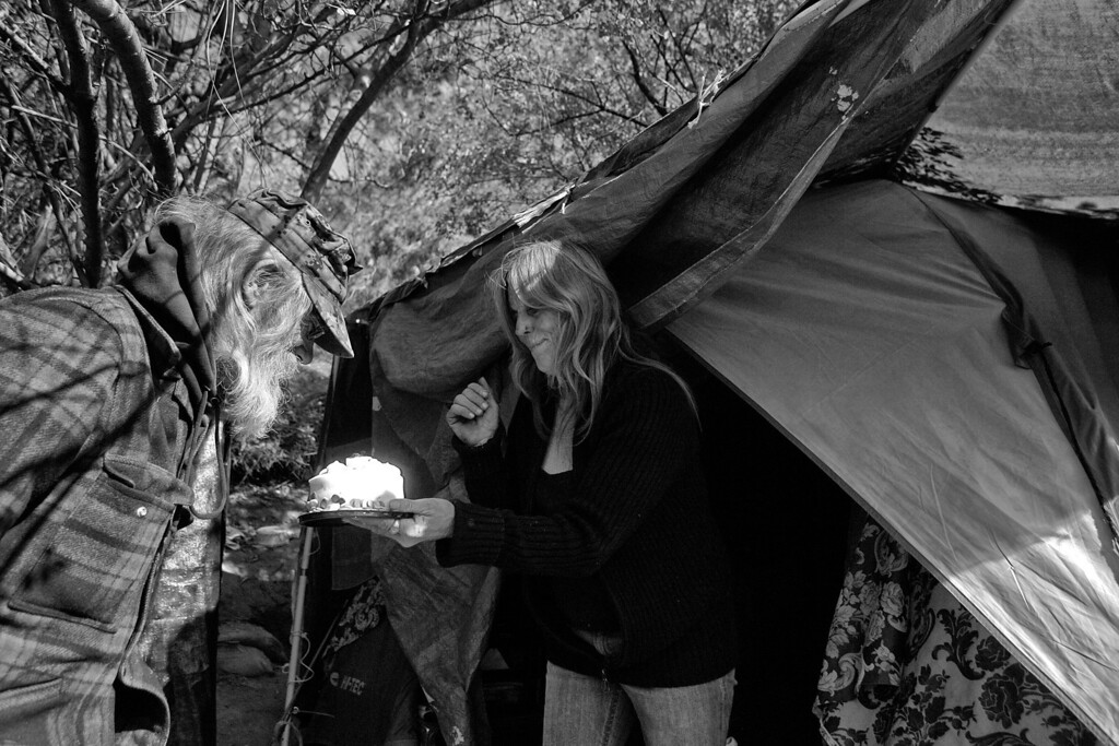 . Dorothy pops out of her tent with a surprise birthday cake for a homeless friend.
