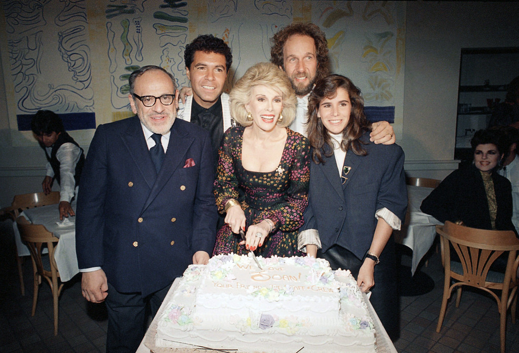 . Comic Joan Rivers, center, cut a cake presented by her staff and crew at a party in her honor at the Columbia Bar and Grill in Los Angeles on Sunday, May 18, 1987. Standing at River\'s side are her husband, Edgar Goldberg, and her daughter Melissa. In the background are announcer Clint Holmes and musical director Mark Hudson. (AP Photo/Reed Saxon)