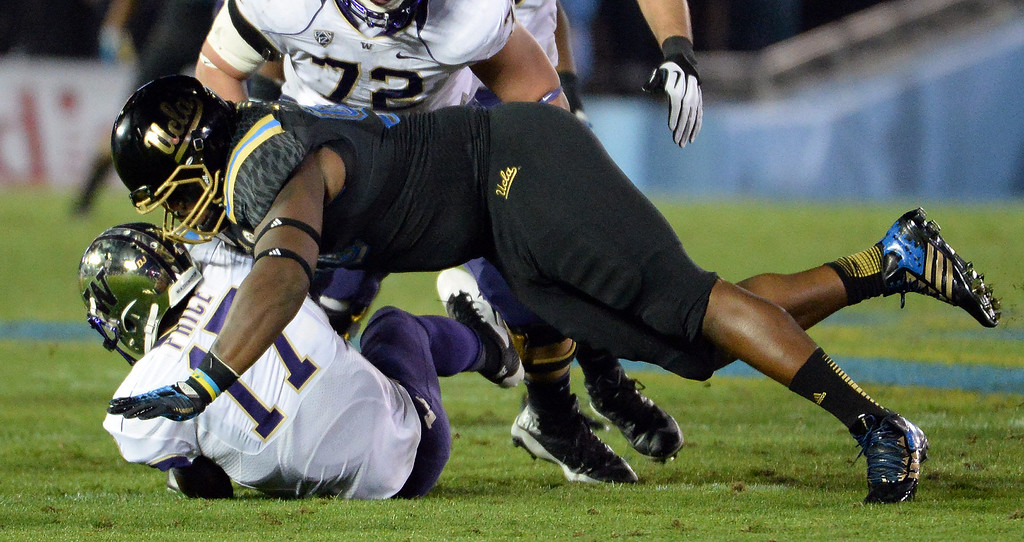 . UCLA Bruins\'s Ellis McCarthy (90) sacks Washington Huskies quarterback Keith Price (17) during the first half of their college football game in the Rose Bowl in Pasadena, Calif., on Friday, Nov. 15, 2013. 
