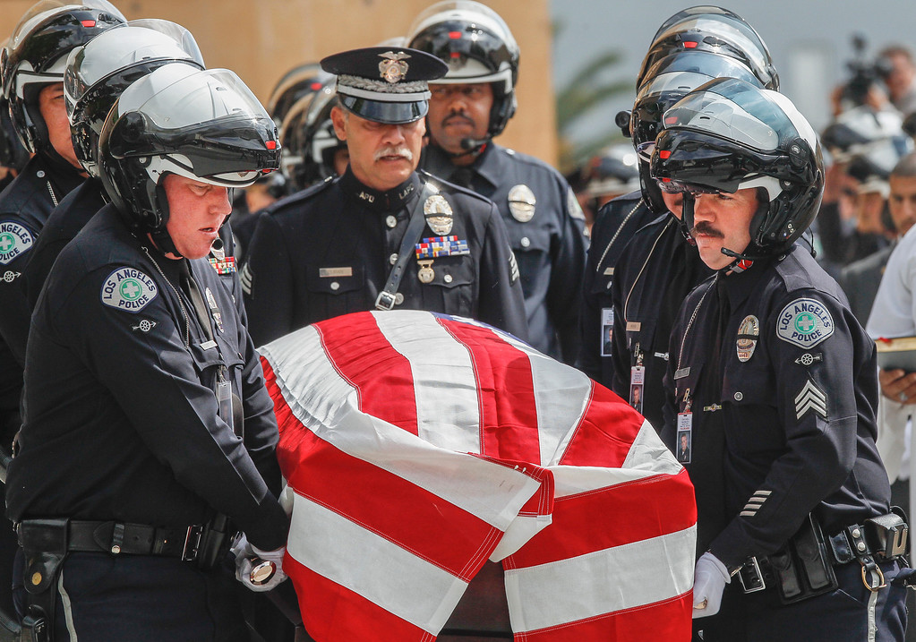 . Pallbearers carry the coffin of Los Angeles Police Dept. motorcycle officer Chris Cortijo after a funeral service at the Cathedral of Our Lady of the Angels Tuesday morning, April 22, 2014, in Los Angeles. Hundreds of fellow law enforcement officers turned out to mourn 51-year-old officer, who died after he was struck by a motorist allegedly under the influence of cocaine on April 5. (AP Photo/Damian Dovarganes)